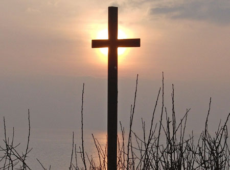 a photo of a cross against a sunset